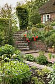 Garten im Mai mit Steintreppe zum reetgedeckten Haus (Ostfriesland, Norddeutschland)