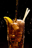 A glass of cola on a black background with large pour, overflowing with bubbles, splashes, straws and lemon