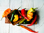 Various colourful chilli peppers in a wooden bowl