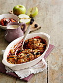 Apple and blackberry crumble with almond flakes