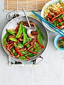 Beef and ginger stir fry with mangetout, peppers and noodles (Asia)
