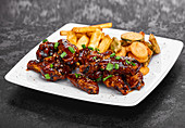 Spicy hot chicken wings cooked with honey and soy topped with sesame seeds served with tempura vegetable and french frites