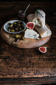 A cheese plate with bread, olives and onion jam