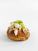 A baked potato with cheese and spring onions