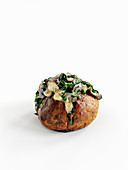 A baked potato with spinach, garlic and mushrooms