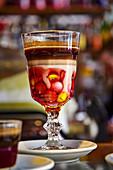 Kakaogetränk mit Schokolinsen in dekorativem Stielglas serviert