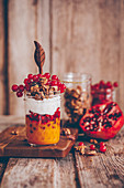 Parfait in a glass with mango pureé, pomegranate seeds, coconut yoghurt and redcurrants