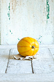 A yellow spaghetti squash against a white wooden background