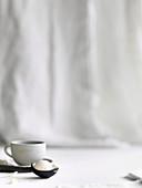 Eisportionierer mit Kugel Vanilleeis vor Kaffeetasse