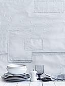 Weiss-graues Geschirr vor weisser Wand
