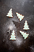 Christmas tree shaped gingerbread cookies with icing, confetti and dusted sugar on top
