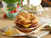 A croissant burger with cheese and egg