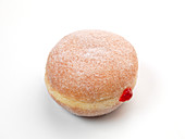 A doughnut filled with red jam against a white background