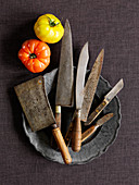 Various vintage knives on a pewter plate (top view)