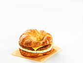 A croissant burger with cheese and egg against a white background