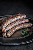 Wagyu bratwurst on a serving dish with a thyme sprig