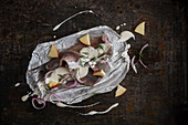 Herring fillets with yoghurt sauce, pieces of apple, shallots, and dill on parchment paper