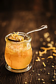 Orange marmalade with orange zest in a glass jar on a wooden background
