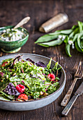 Wild herb and asparagus salad with tomatoes, raspberries and wild garlic cream