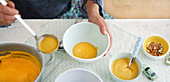 Sweet potato and almond soup being ladled into bowls