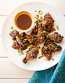 Grilled honey and sesame seed chicken wings on a white wooden table