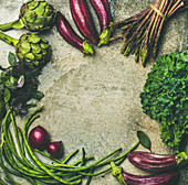 Green and purple raw vegetables: Eggplans, beans, kale, asparagus, artichoke, basil