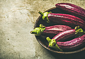 Purple eggplants in wooden bowl