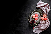 Macarons on a silver platter against a dark bckground
