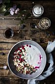Frühstücksmüsli im Schälchen auf rustikalem Holztisch (Aufsicht)