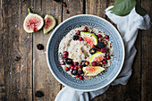 Breakfast porridge with figs and blackberries in a bowl on a rustic wooden table
