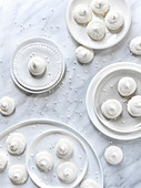 White meringue cookies on white plates on a light marble surface with pearl sprinkles scattered around the frame