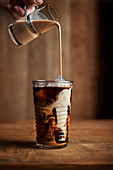 Glass of iced coffee with vintage creamer pouring into the glass on warm wood tones