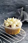 A pumpkin and walnut cupcake with lime cream