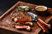 Gegrilltes New York Striploin Steak mit Pfeffersauce und Besteck auf Holzbrett