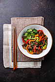 Szechuan beef stir fry with vegetables in bowl on dark background