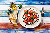 Watermelon salad with feta cheese, balsamic sauce and mint on wooden background
