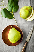 Fresh, ripe pears in a copper bowl on a natural linen