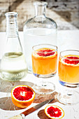 Blood orange spritzers with lime on a table outdoors