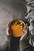 Bowl of vegetarian pumpkin carrot soup served with saffron salt, croutons and onion