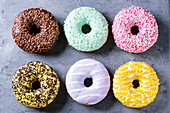 Variety of colorful glazed donuts over gray metal texture background