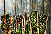 Raw organic purple carrot with chard mangold leaves over old wooden plank background