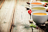 Variety of cream soups - tomato, broccoli and pumpkin soups over wood background