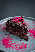 A slice of lactose-free chocolate beetroot cake with raspberry powder