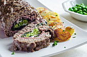 Meatloaf filled with peas and ham with fried potatoes