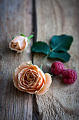 Peach-coloured roses and raspberries on a wooden surface