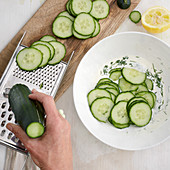 Cucumbers being sliced for a salad