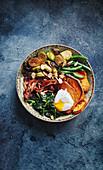 Bowl mit grünem Gemüse, Süsskartoffeln, Pancetta und Ei