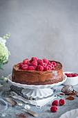 Schokoladenkäsekuchen mit frischen Himbeeren auf Kuchenständer