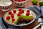 Vegan avocado and lime tart with raspberries, sliced