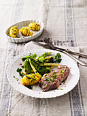 Aromatically steamed beef steaks with beans, peas and potatoes